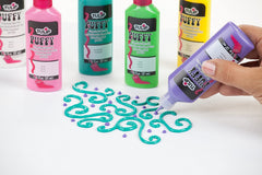 Tubes of Puffy Paint and a hand painting a curly design with a teal puffy paint.