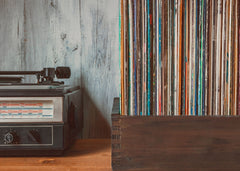 half of a record player is showing and then a wooden box filled with records