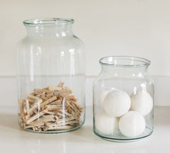 2 glass jars filled with cotton balls and clothes pins