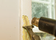 Heat gun and scrapper being used to pull paint off the trim of a window.