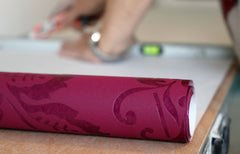 Magenta roll of wallpaper, a hand is rolling it out.