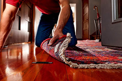 Muscular man on hands and knees applying rug anchor to a corner of a rug.
