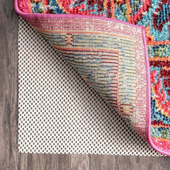 Corner of a rug folded up showing the white rug gripper below
