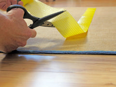 Hand cutting yellow rug tape on the backside of a rug.
