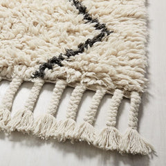 Close up of corner of a thick white wool rug with a black design on it.