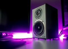 Speaker next to a computer screen with neat purple lighting background