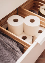 Open white vanity bathroom drawer with toilet paper rolls and towels inside.