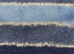 Close up of a high pile blue and white striped rug