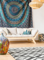 Bohemian looking living room, with a cream sofa.  Large circular tapestry above the sofa.  Wicker hanging lights.