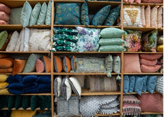 Shelves filled with all shapes and colors of throw pillows.