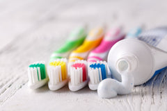 Green toothbrush next to a yellow toothbrush, then pink and blue, and then the toothpaste tube is open and squeezing out.