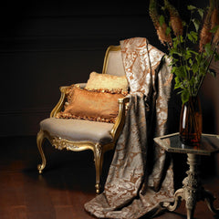 Traditional chair with gold pillows and a damask fabric draped over it.