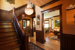 Looking into a historic home with wood molding, trim and stairs.