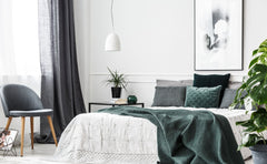 White bedroom, gray curtains, blue, gray and green accent pillows.