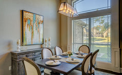 Dining room table with more traditional rounded back chairs, a modern light fixture and art piece above a more modern buffet piece.