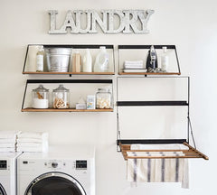 Close up of wall with dryer and shelves above with metal letters Laundry above
