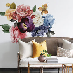 Simple sofa with large flowers on the wall behind it.