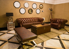 Beige living room with oversized leather sofas and behind the large sofa is a grouping of mirrors