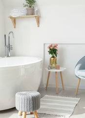White bathroom focus is on the white bath tub, next to the tub is a table with flowers on it and chair, in front of the tub is a stool and a woven rug.