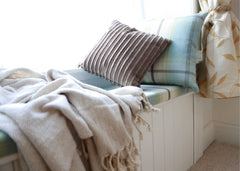 Window seat with pillows and blankets on top