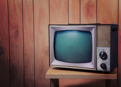 An old tv in front of a wood paneled wall.