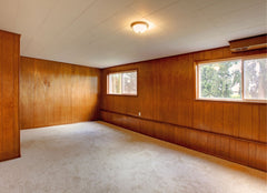 An empty room where all the walls are wood paneling.