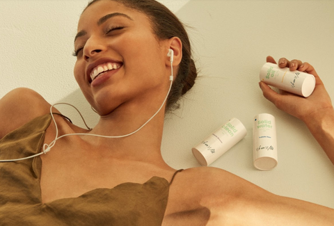 Alt text: A person in a brown tank top listens to music, holding We Are Wild skincare products.