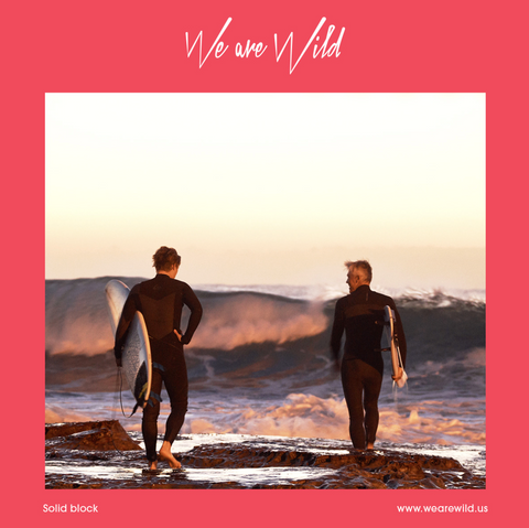 Alt text: Two people with surfboards walk towards the waves.
