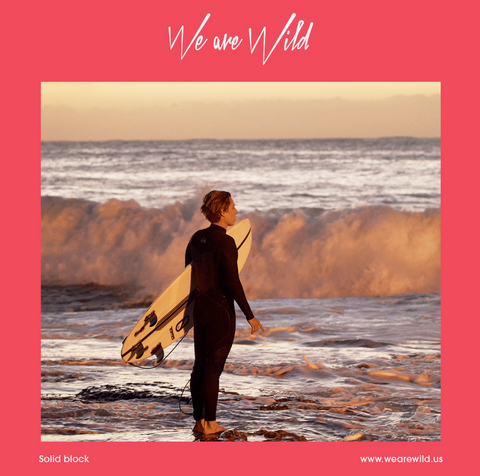 alt text: A person holding a surfboard looks at the water as the sun sets.