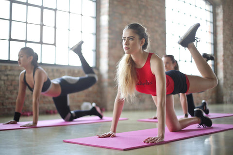 Alt Text: A woman in a red tank top does yoga with her yoga class