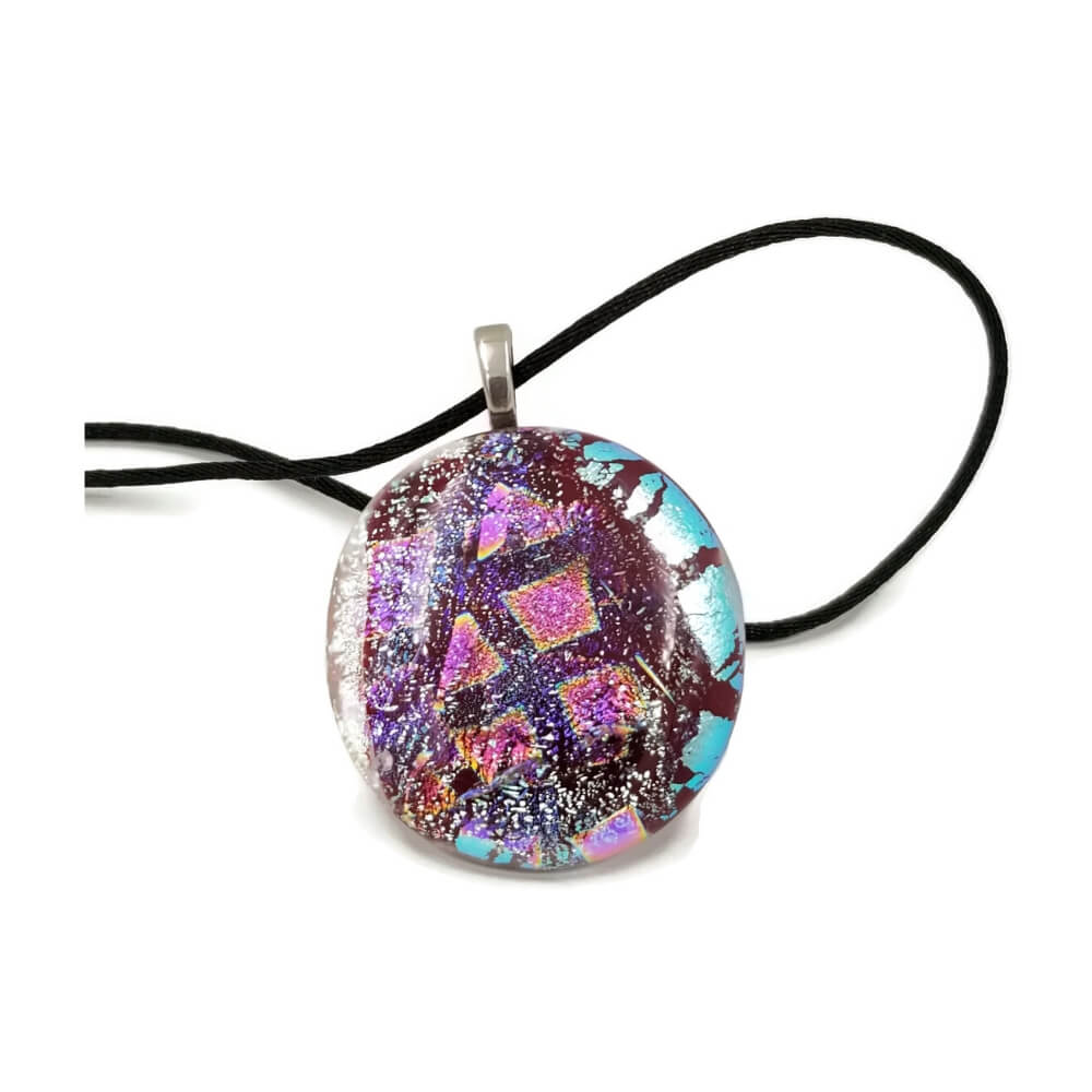 Dichroic glass pendant by artist Cristine Grimm features silver and light turquoise shimmer on a field of cranberry red, suspended on a silver colored bail and black necklace.