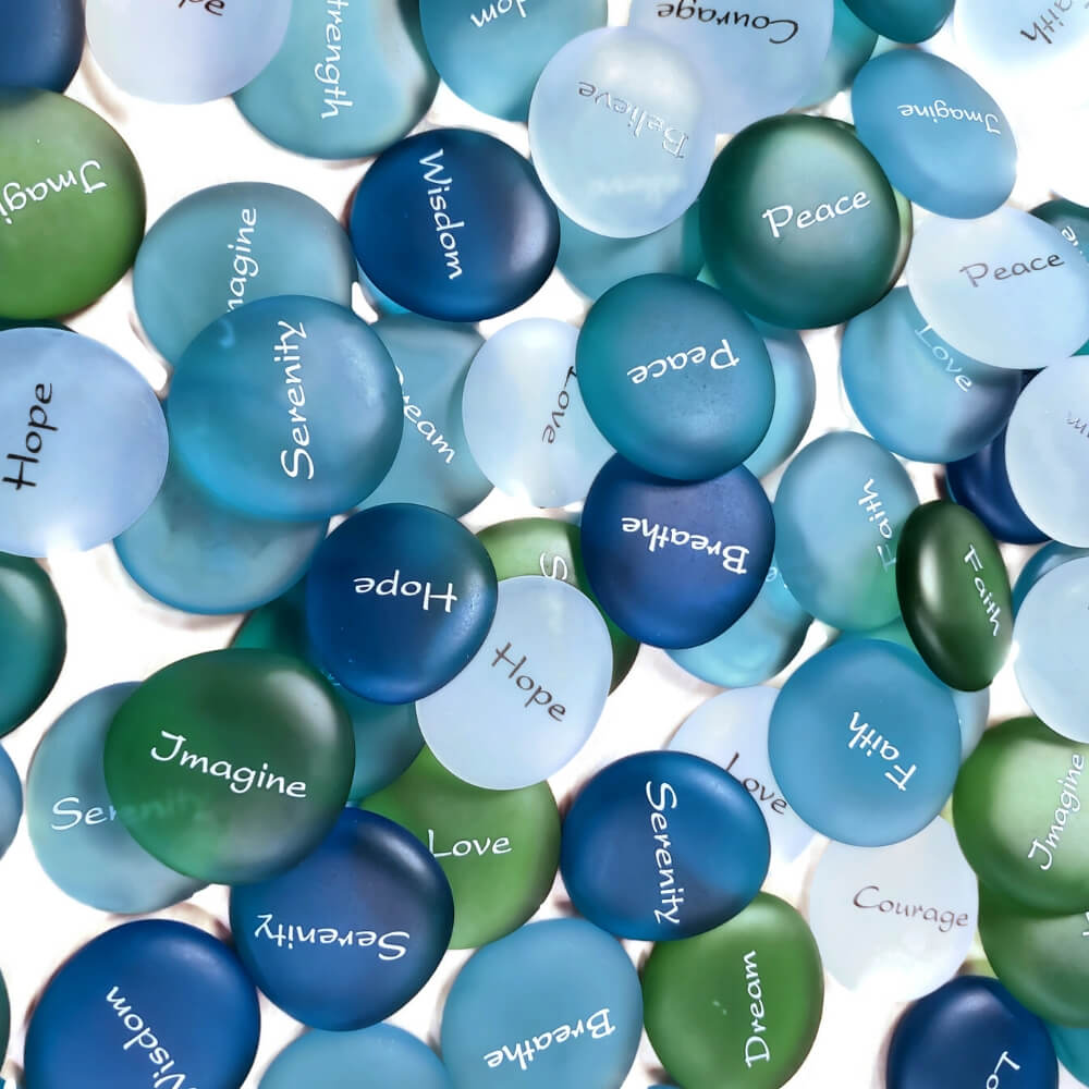 "Smooth blue, teal, green, light blue and white glass ""stones"" with a word written on each in white. Words include Serenity, Hope, Imagine, Wisdom, Peace, Breathe, Faith, Dream, and Love."