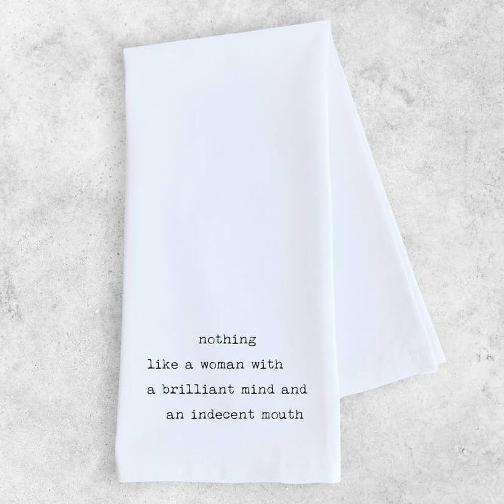 "White kitchen/tea towel with black lettered words stating ""Nothing like a woman with a brilliant mind and an indecent mouth""."