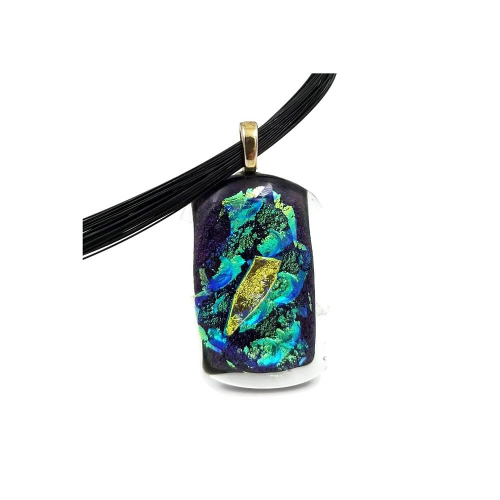Rectangular glass pendant with a gold bail and partial view of a black necklace. The pendant is made of dichroic glass in a deep purple with accents of blue, green, black, teal, and gold.