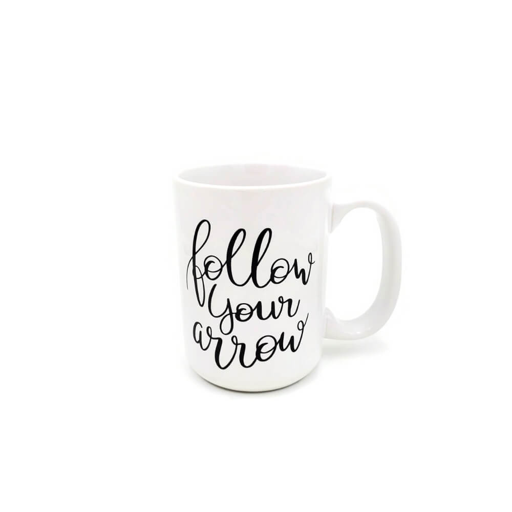 "White ceramic mug featuring black script reading ""Follow Your Arrow""."