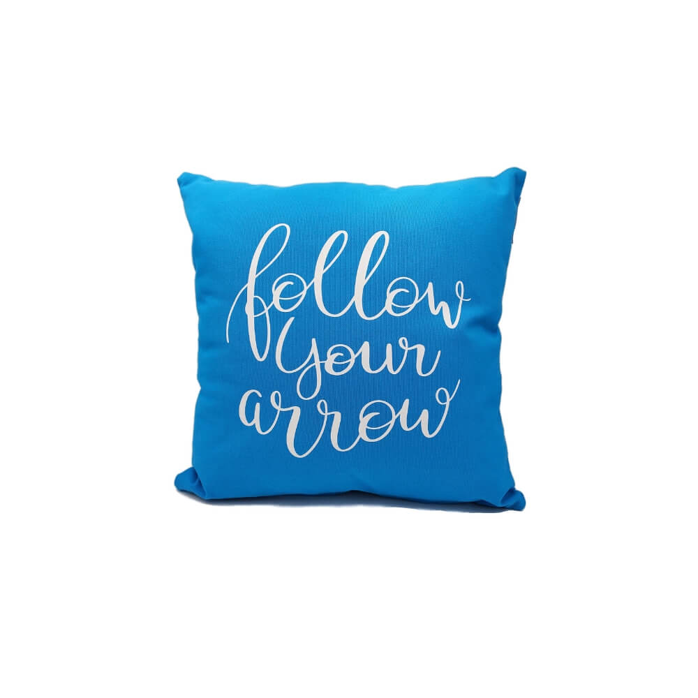 "Cerulean blue square stuffed pillow with white script and the quote ""Follow your Arrow""."