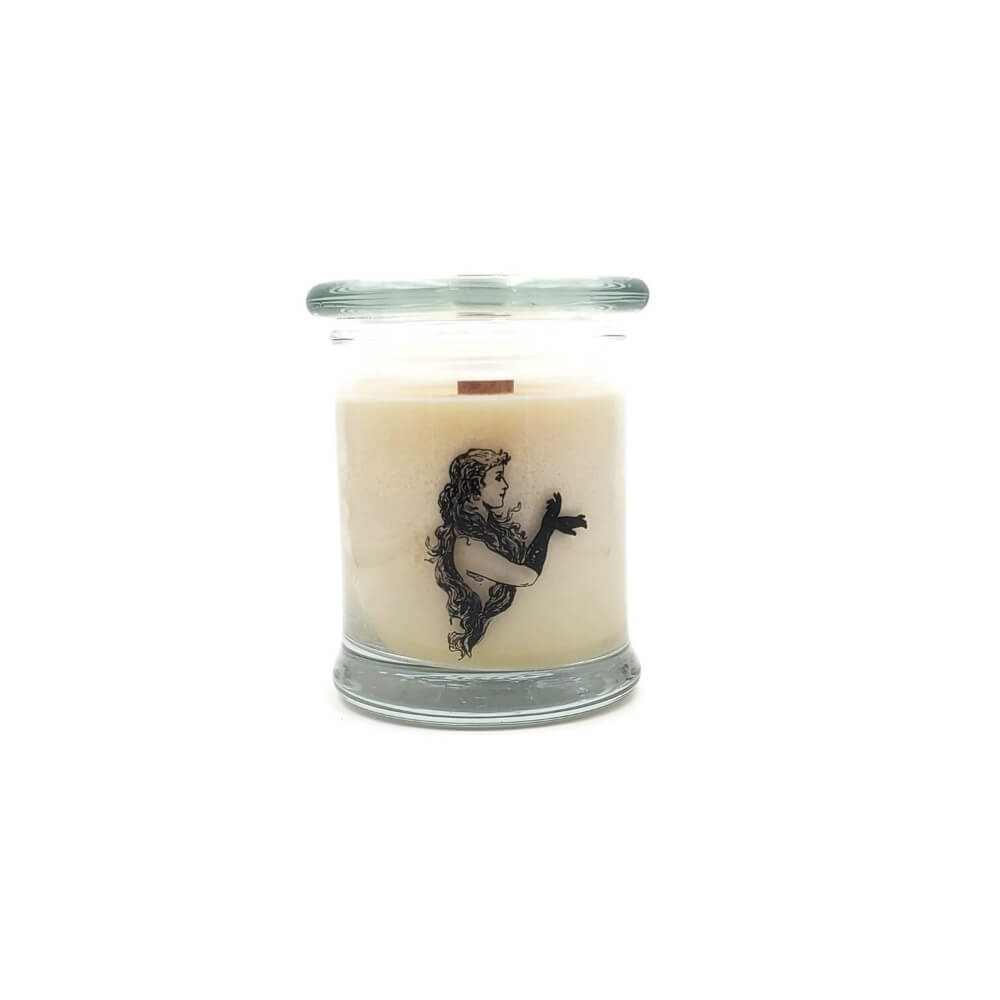 Anise Scented soy candle with a wood wick, inside a glass jar with a lid. There is a decal of a woman with long, curly black hair wearing elbow length black gloves on the side of the glass.