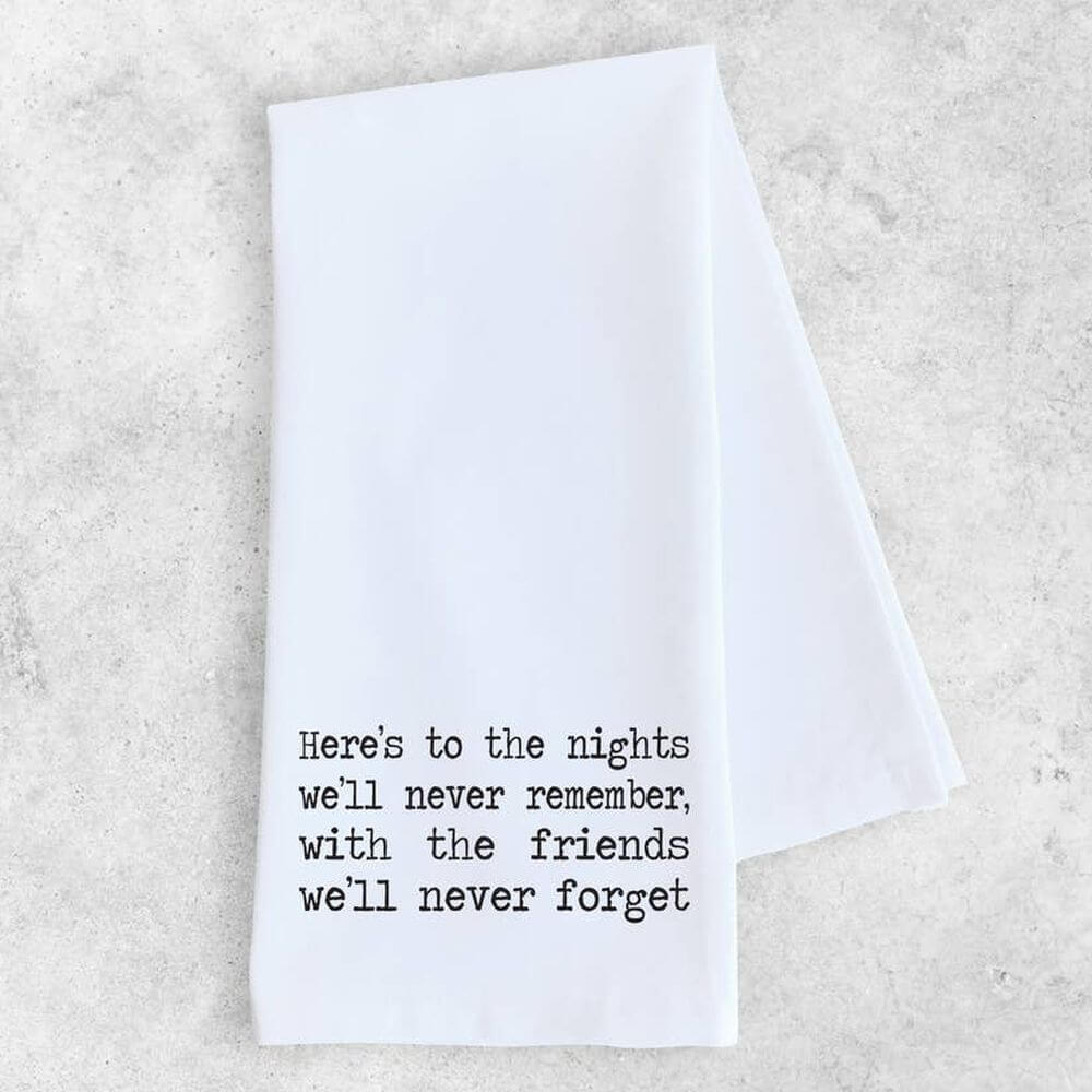 "White cotton kitchen towel with typewriter font in black  which reads ""Here's to the nights we'll never remember, with the friends we'll never forget."""