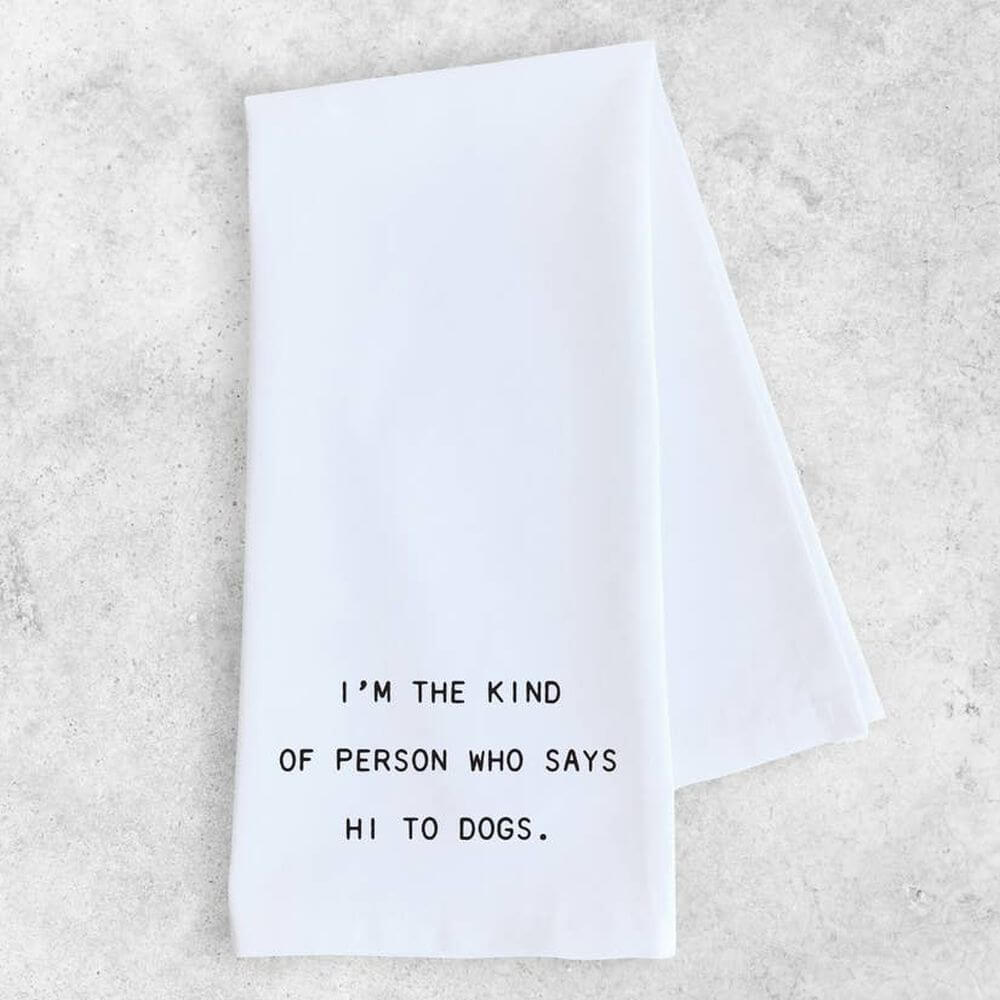 "White cotton tea or kitchen towel with typewriter style font saying ""I'm the kind of person who says hi to dogs""."