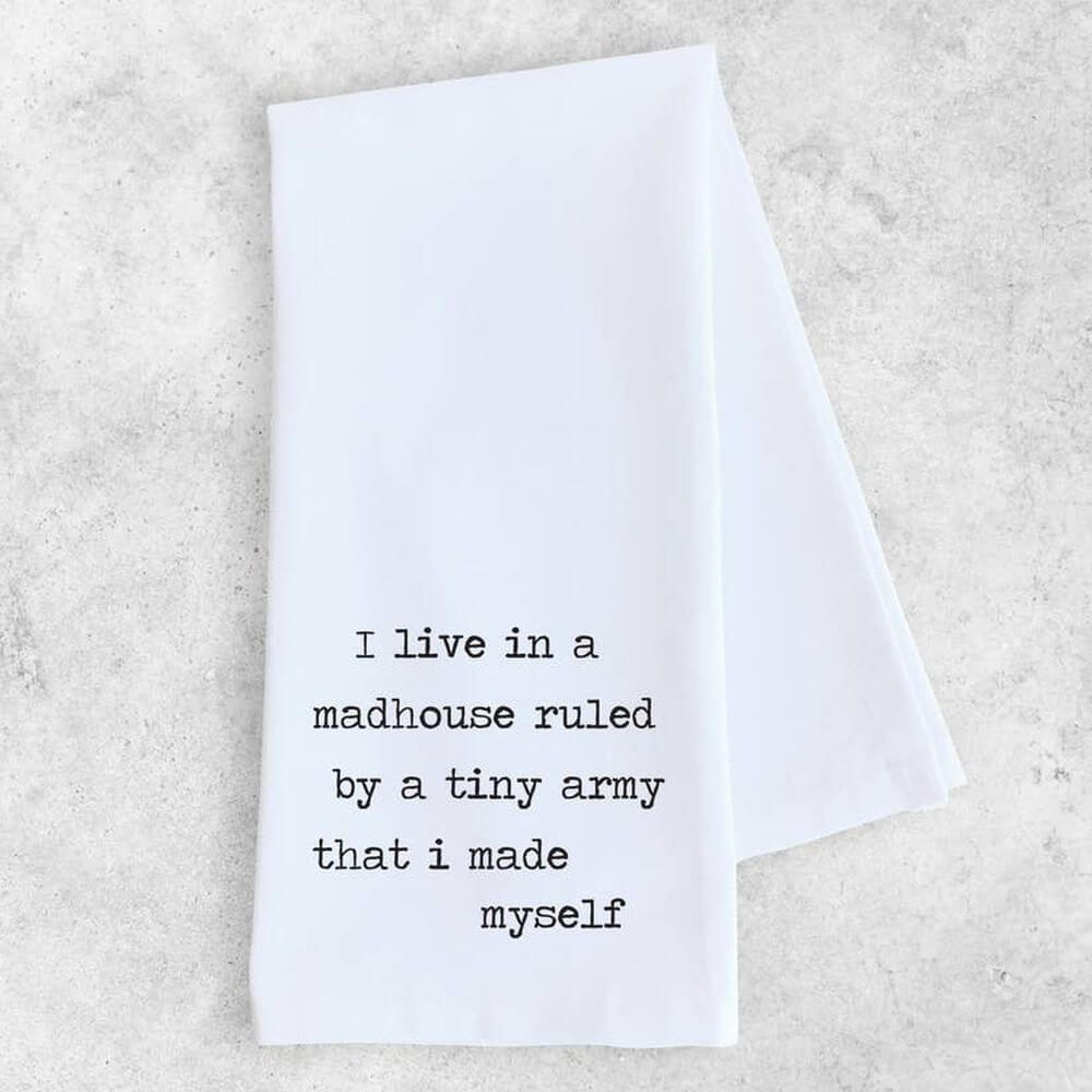 "White cotton tea or dish towel with black typewriter font quote reading ""I live in a madhouse ruled by a tiny army that I made myself""."