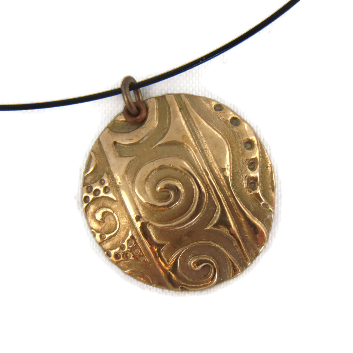 Geometrically textured  large bronze circle pendant made from BronzClay metal clay and suspended on a black, cable wire necklace.