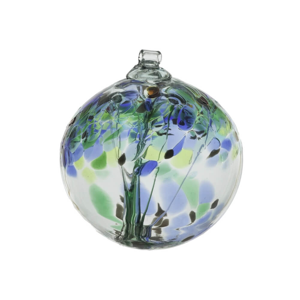 A clear glass blown glass ornament with accents of blue and green. There are strands of glass suspended through the middle of the ornament.
