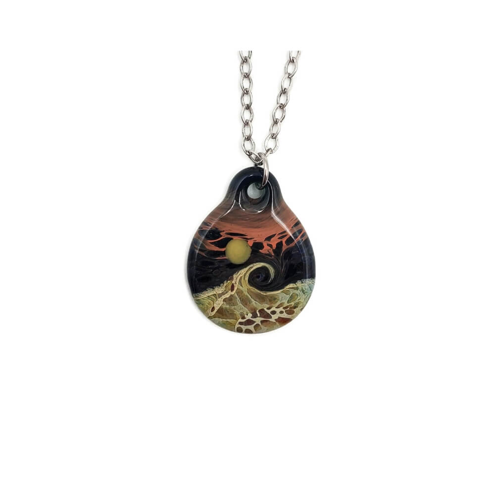Dark colored, round pendant with a mottled green wave under a yellowish green moon or sun. The sky is a mixture of the dark color and salmon.