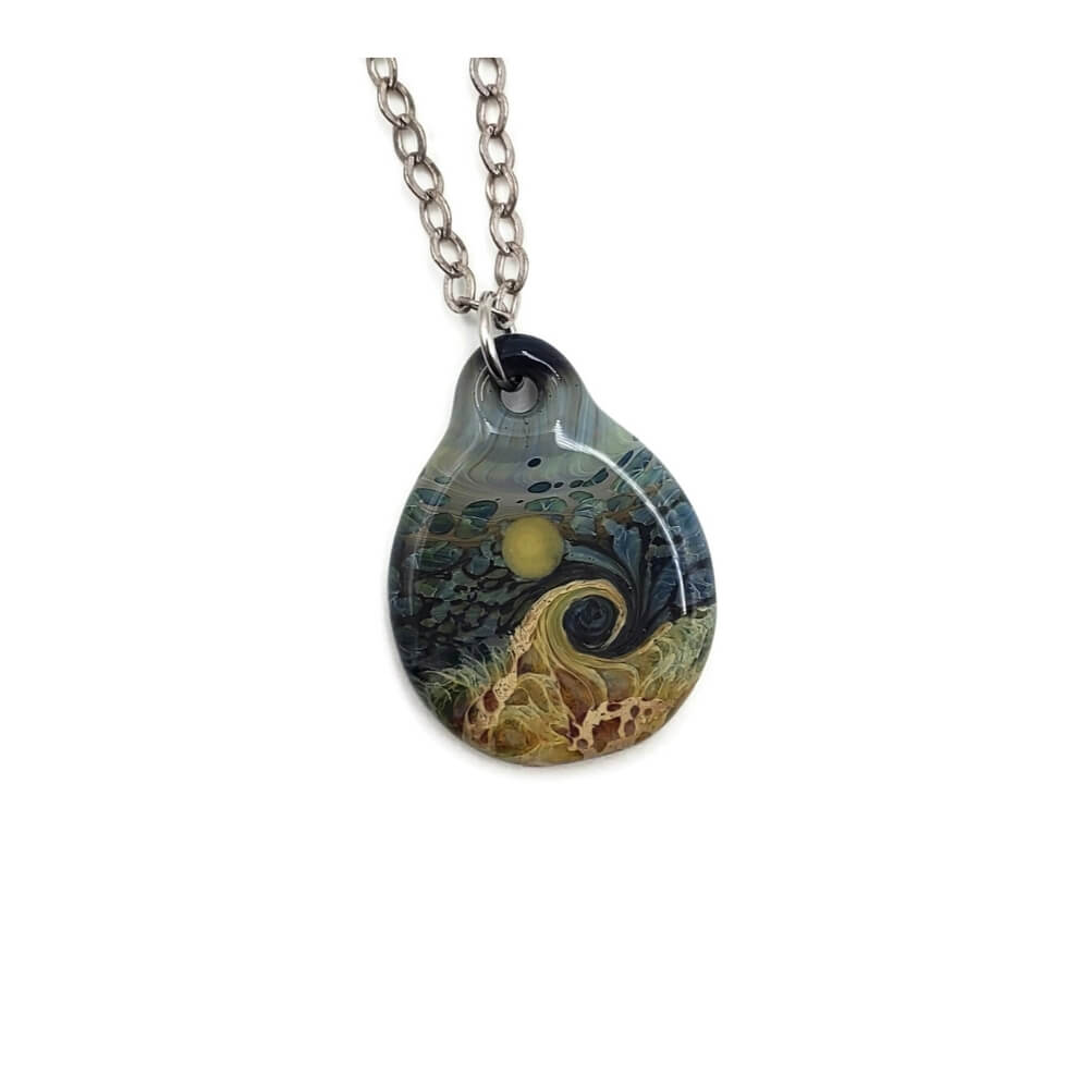 Round glass pendant on a silver colored chain. The pendant features a beach scene, with brown, green, and yellow sand and dune grass, A wave seems to crash on the beach underneath a blue & green mottled sky with a yellow sun or full moon.
