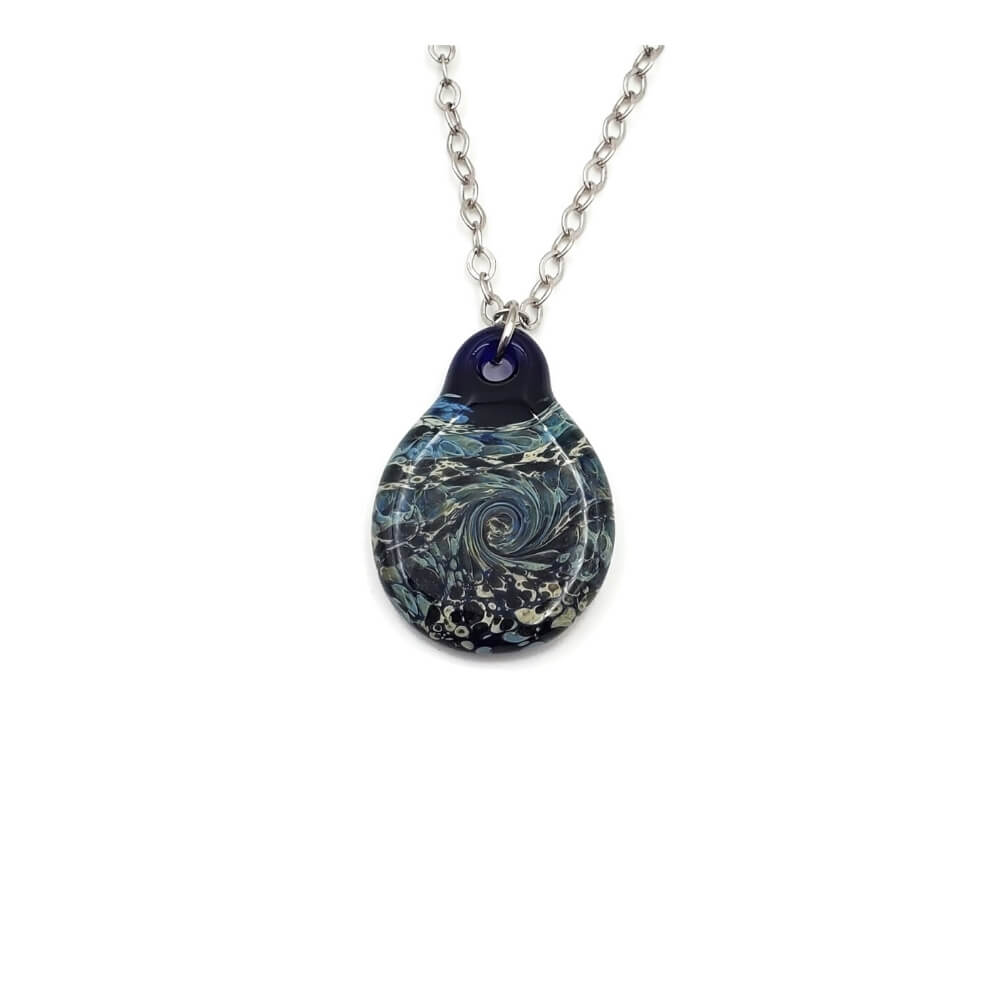 Dark blue pendant hanging on a silver tone chain. The pendant features swirling colors of sage, light blue, medium blue, and cream.
