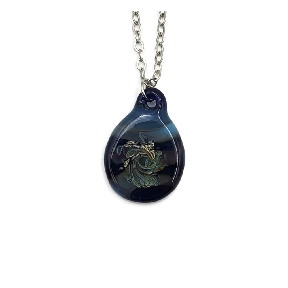 Denim  blue glass pendant hanging on a silver tone chain. The pendant features  the abstract image of a wave made of sage and cream.
