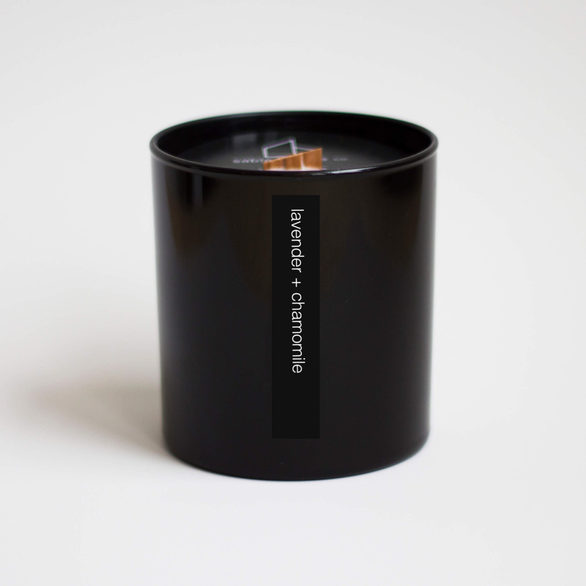 "A tall black container holding a beige candle with a wood wick. White words read ""lavender + chamomile"".""."