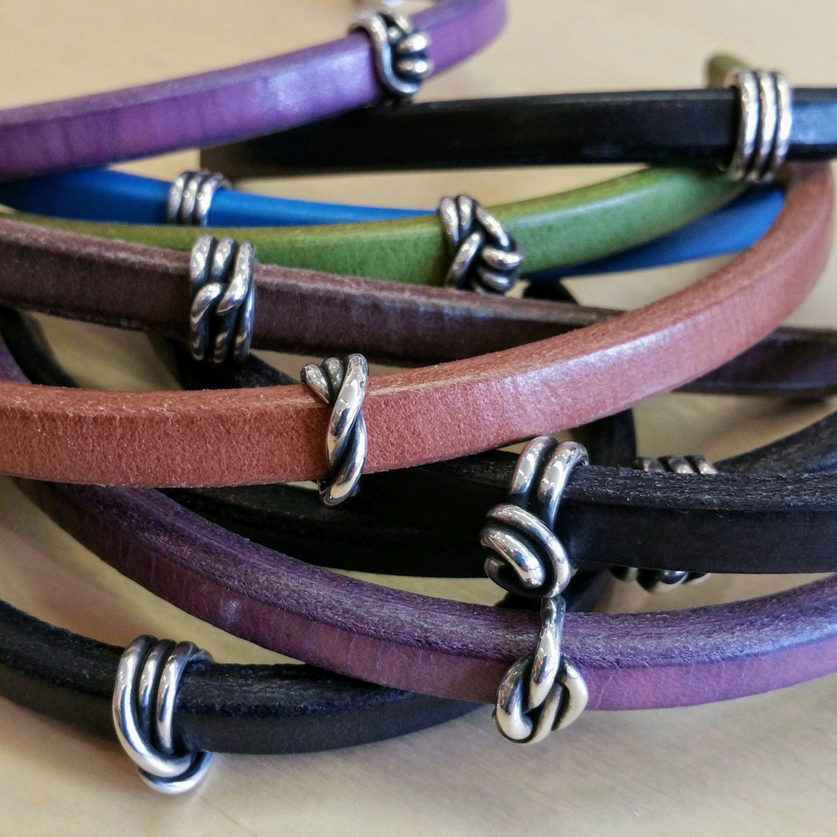 Various colored leather bracelets featuring  wrapped silver beads made from fine silver clay. Each bead is a different style wrap.