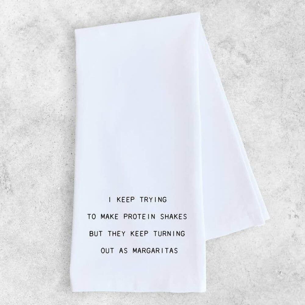 "A white kitchen/tea towel with black typewriter style letters reading ""I keep trying to make protein shakes but they keep turning out as margaritas""."