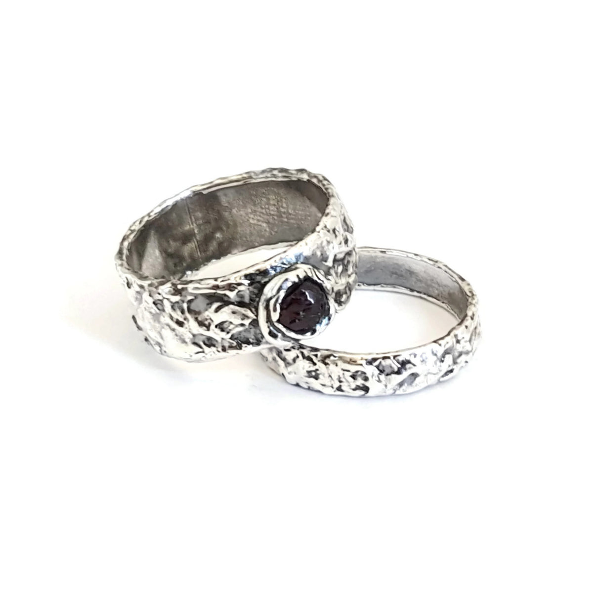 Two textured fine silver rings made with silver metal clay. One features a raw garnet gem-stone.